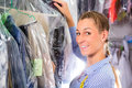 Cleaner in laundry shop checking clean clothes female or textile dry cleaning next to garment bags Stock Photos