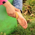 Cleaning bare foot of a little girl her sole with leaf Royalty Free Stock Photo
