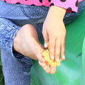 Cleaning bare foot of a little girl her sole with leaf Stock Image
