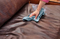 Cleaning chores closeup of hand and conditioning a leather couch with conditioning product and blue microfiber cloth Stock Images