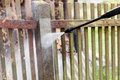 Cleaning dirty garden fence post with high pressure washer Royalty Free Stock Photo