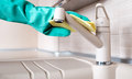 Cleaning the faucet hands in rubber gloves in kitchen Royalty Free Stock Image