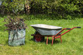 Cleaning in the garden, wheelbarrow and compost sack on the lawn Royalty Free Stock Photo