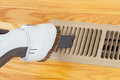 Cleaning heater vent withvacuum horizontal photo of vacuum floor with red oak floors in background Royalty Free Stock Photos