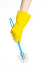 Cleaning the house and cleaning the toilet: human hand holding a blue toilet brush in yellow protective gloves isolated on a white Royalty Free Stock Photo