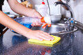 Cleaning kitchen with spray and sponge Royalty Free Stock Photo