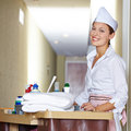 Cleaning lady doing housekeeping in hotel happy with cart Stock Photos