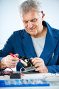 Cleaning old iron senior adult electrician with soft brush before repairing Stock Photography