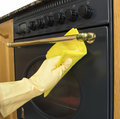 Cleaning the outside of an oven women arms only Royalty Free Stock Images
