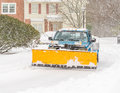 Cleaning road after snowstorm snow plough truck clearing whiteout winter blizzard for vehicle access Royalty Free Stock Photo