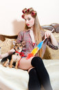 Cleaning service: beautiful little dog with red ribbon sitting with pinup girl in bed seriously looking at camera Royalty Free Stock Photo