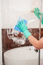 Cleaning a shower glass man wearing gloves with rag Royalty Free Stock Photography