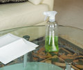 Cleaning solution spray bottle on top of dirty glass table photo in with paper towels and sofa in background Royalty Free Stock Images