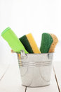 Cleaning sponges in a silver pail on white wooden table Stock Photo