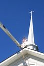 Cleaning the steeple a man in a bucket lift a mildew covered church Stock Images