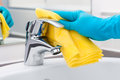 Cleaning tap woman doing chores in bathroom Stock Photo