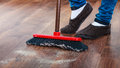 Cleaning woman sweeping wooden floor cleanup housework concept closeup broom and female foots Royalty Free Stock Photography