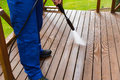Cleaning wooden terrace with high pressure washer Royalty Free Stock Photo