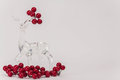 Clear glass reindeer surrounded by ornamental cranberries on white background with empty space for text Royalty Free Stock Image