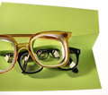 Clear view through high diopter glasses two pairs of eyeglasses on creative support made of green paper photographed on white Stock Photo