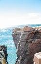 Cleft in coastal cliff steep rockly cliffs on sunny coast Stock Photos