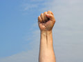 Clenched fist with a blue sky background being held up Royalty Free Stock Photography