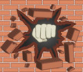 Clenched fist breaking through red brick wall Royalty Free Stock Photo