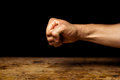 Clenched fist fish on black background above wooden surface Royalty Free Stock Photo