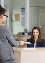 Clerk is handing over a document to a customer caucasian in the background client latin in the foreground at reception counter in Royalty Free Stock Photos