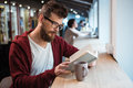 Clever boy in glasses reading book sitting at the desk serrious handsome and brown hoodie a Stock Image