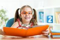 Clever cute child girl wered eyeglasses with book Royalty Free Stock Photo