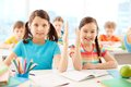 Clever girls portrait of two diligent raising hands at workplace with classmates on background Stock Photos