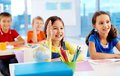 Clever kids schoolkids raising their hands to answer the question Stock Photography