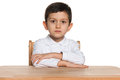 Clever pensive little boy sits at the desk and looks forward Royalty Free Stock Photos