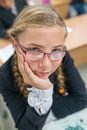 Clever schoolgirl cute wearing glasses drawing in copybook and looking at camera Stock Photo