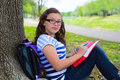 Clever student teen girl with school bag under park tree teenager resting relaxed Stock Photography