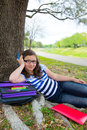 Clever student teen girl with school bag under park tree teenager resting relaxed Royalty Free Stock Image