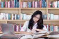 Clever teenage girl doing assignment in the library portrait of a high school student with long hair studying while her Royalty Free Stock Photo