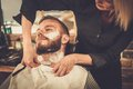 Client in barber shop during beard shaving Stock Images