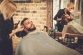 Client during beard and moustache grooming in barber shop Royalty Free Stock Image