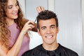 Client getting haircut from hairdresser portrait of happy female at salon Stock Photo