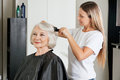 Client having hair straightened by hairstylist female at salon Stock Photo