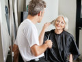 Client instructing hairdresser in salon senior female male beauty Royalty Free Stock Photography