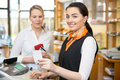 Client at shop paying at cash register with saleswoman Royalty Free Stock Photos