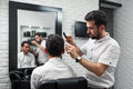 Client watching prosess of combing hair by hairstylist is carefully brushing s in barbershop and the process in reflection in the Royalty Free Stock Photo
