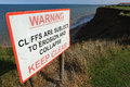 Cliff collapse warning sign at top of soft clay cliffs near skipsea yorkshire Royalty Free Stock Images
