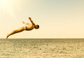Cliff diver jumping in the sea against the sky at sunset Royalty Free Stock Photo