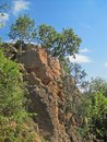 CLIFF FACE NEXT TO A RIVER WITH DENSE GREEN VEGETATION Royalty Free Stock Photo