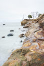 Cliff by the sea near and several rocks in water on a overcast day Stock Photography