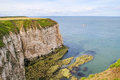 Cliffs at flamborough head with boat in distance yorkshire england Royalty Free Stock Photo